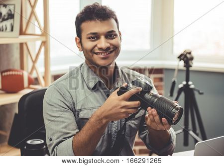 Attractive Afro American photographer is holding his camera and smiling while sitting in his office