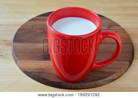 Fresh milk in big red cup on dark nutwood platter