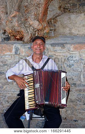 AGIOS NIKOLAOS, CRETE - SEPTEMBER 17, 2016 - Cretan man playing the piano accordion in the port Elounda Crete Greece Europe, September 17, 2016.