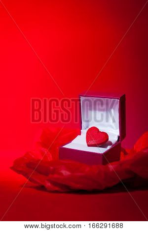 A most precious valentine themed still life image of a red love heart in a gift box. Red background with copy space.