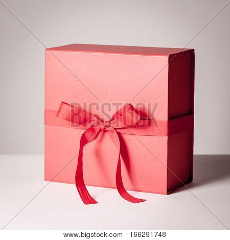 A luxurious gift in a red box tied with a red ribbon isolated on white.