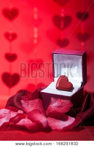 A romantic still life of a red heart in a gift box surrounded by rose petals and other symbols of love and Valentines day.