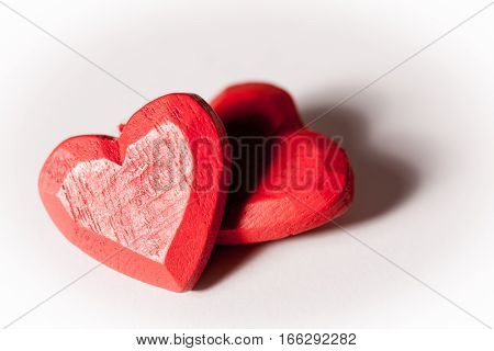 Love hearts. A pair of red wooden love hearts isolated on white.