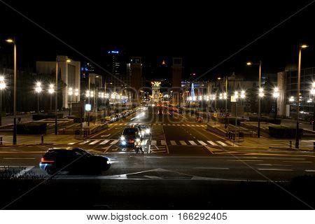 Barcelona Spain - December 1 2016: Avinguda de la Reina Maria Cristina street at night in Barcelona Spain. Unidentified people visible.