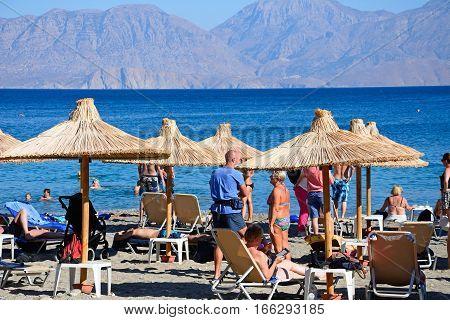 AGIOS NIKOLAOS, CRETE - SEPTEMBER 17, 2016 - Tourists relaxing on the beach with views towards the mountains Agios Nikolaos Crete Greece Europe, September 17, 2016.