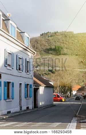 THANN FRANCE - DEC 12 2015: Traditional timbered house with an impressive view of the Alsatian vineyars hills- Route des Vins seen at the end of the street with impressive view to the Croix du Rangen