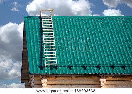 Part of new wooden country house from logs and green metal tile roof against blue sky with white clouds