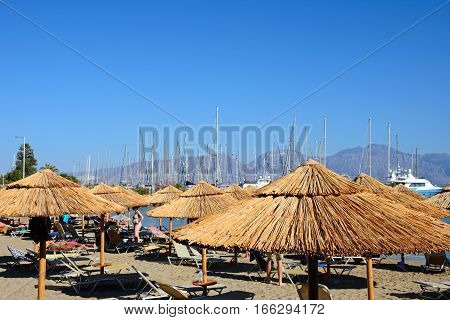AGIOS NIKOLAOS, CRETE - SEPTEMBER 17, 2016 - Tourists relaxing on the beach with views towards the marina Agios Nikolaos Crete Greece Europe, September 17, 2016.
