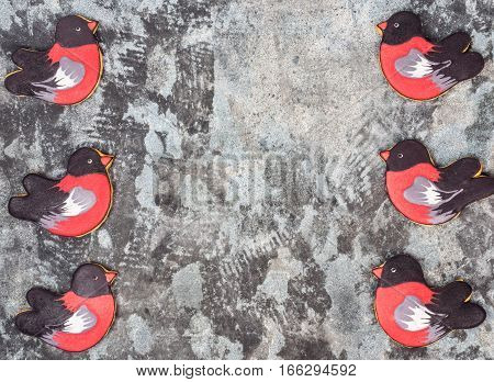 Gingerbread cookie in the shape of birds bullfinches six pieces facing each other. Sweet cookies bullfinches on a gray grunge background
