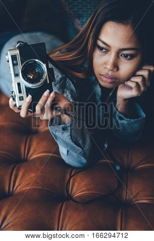 Save Download Preview Gorgeous girl lying on leather sofa with photo camera in her hands
