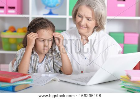 Portrait of a granny with her granddaughter using laptop