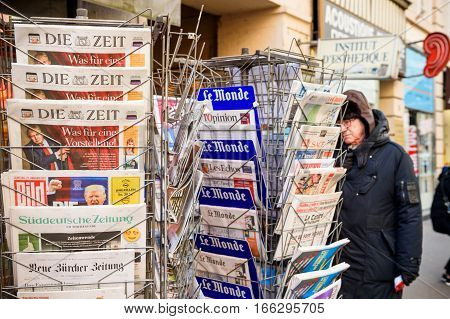 PARIS FRANCE - JAN 21 2017: Man purchases a International newspapers from a kiosk newsstand featuring headlines with Donald Trump inauguration as the 45th President of the United States in Washington D.C