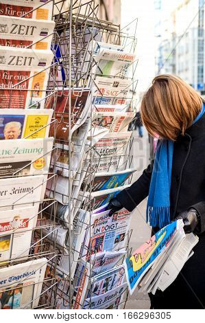 PARIS FRANCE - JAN 21 2017: Woman purchases Un Doigt (A Finger) French newspaper from a newsstand featuring headlines with Donald Trump inauguration as the 45th President of the United States in Washington D.C