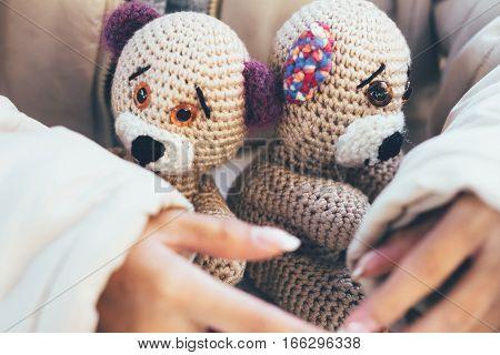 Girl hands gently hugging two teddy bears