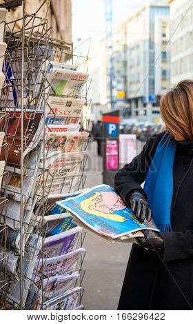 PARIS FRANCE - JAN 21 2017: Woman purchases Charlie Hebdo French satire newspaper from a newsstand featuring headlines caricature with Donald Trump inauguration as the 45th President of the United States in Washington D.C