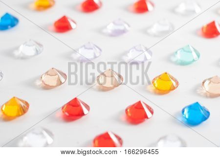 A collection of different faceted stones on a white background, pattern of multicolored precious jewelry