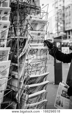 PARIS FRANCE - JAN 21 2017: Woman purchases a le canard enchaine l'alsacela croiz charlie hebdo French newspaper from a newsstand featuring headlines with Donald Trump inauguration as the 45th President of the United States in Washington D.C