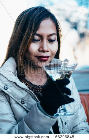 Beautiful adult girl drinking Martini outdoor , early spring
