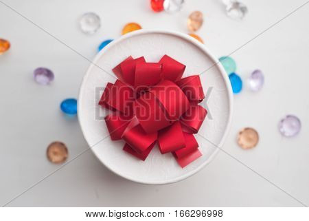 Round box with red bow, view from the top, scattered red hearts and decorative stones, Valentine's day, festive background