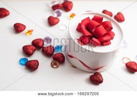 Round box with red bow, scattered red hearts and decorative stones, Valentine's day, festive background