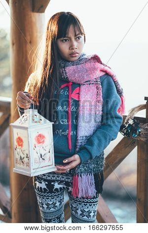 Beautiful girl wearing scarf, holding lantern during sunset