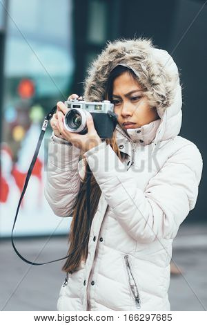 Beautiful girl in a winter coat photographing outside, urban environment
