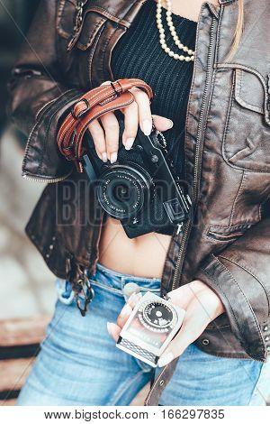 Girl hands holding camera and vintage light meter