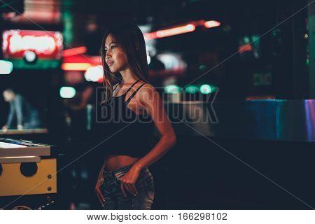 Sexy tan Asian girl standing in a club