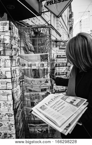 PARIS FRANCE - JAN 21 2017: Woman purchases a USA TODAY WEEKEND newspaper from a newsstand featuring headlines with Donald Trump inauguration as the 45th President of the United States in Washington D.C