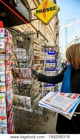 PARIS FRANCE - JAN 21 2017: Woman looking at international press newspapers from a newsstand featuring headlines with Donald Trump inauguration as the 45th President of the United States in Washington D.C