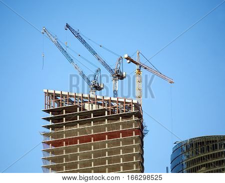 Hoisting tower cranes in construction process on top of office building construction over clear blue sky