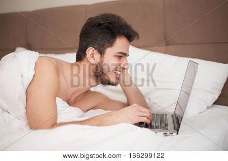 Young smiling man using laptop in bed at home