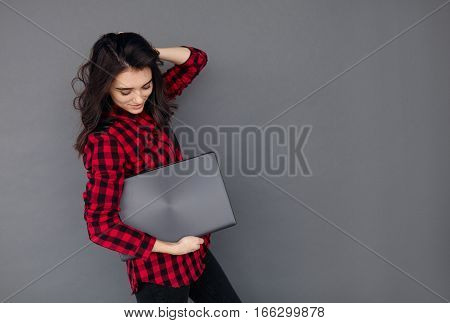 Casual young woman holding a brand new laptop over grey background with copy space
