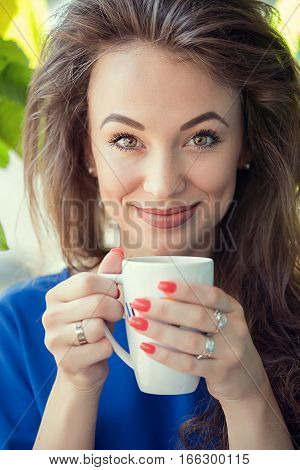 Woman Drinking A Cup Of Coffe In A Cafe