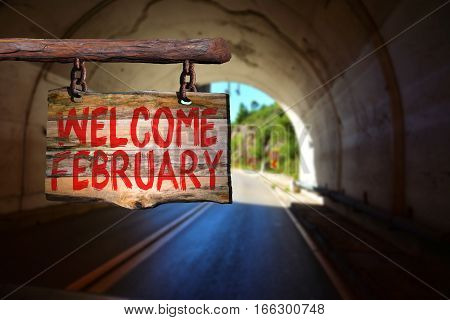 Welcome february motivational phrase sign on old wood with blurred background
