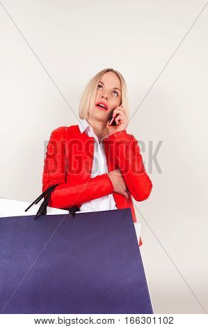 Portrait of young woman in a red jacket with shopping bags on a white background. Woman with shopping bags talking on the phone.