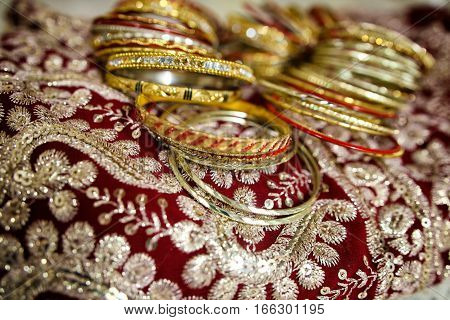 Gold Indian women's bracelets lie on a sari.