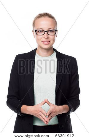 Portrait of beautiful smart young businesswoman in business attire wearing black eyeglasses, standing against white background with arms steeple .