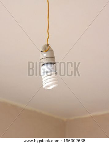 Electrical Energy saving light bulb in white chuck hanging on yellow wire closeup