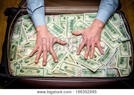 man holding hands on a suitcase with US currency
