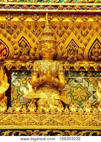 Gold carvings of celestial deities on the walls of kings palace Bangkok