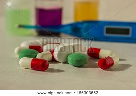 Medications and a thermometer on a light background. Concept - medicine treatment.