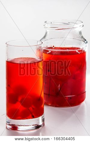 Cherry Compote In A Jar In A Glass On A White Background.