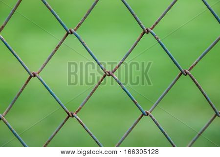 Close focus on pattern square wire wall covered by rust with blurry background of green grass yard.