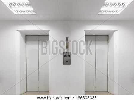 Two elevators inside white building at first floor with light on ceiling. Emergency telephone attached above button between elevators.