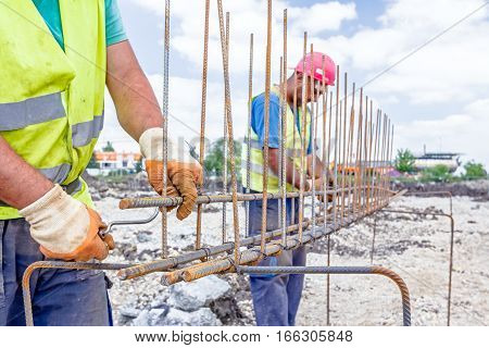 Worker is tying rebar to make a newly constructed footing frame. Binding concrete frame