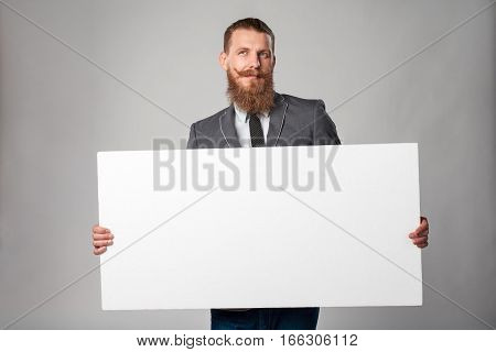 Hipster business man with beard and mustashes in suit standing holding white banner, looking up in thoughts daydreaming, over grey background