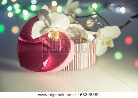 gift box in form of heart on the background of the white orchid
