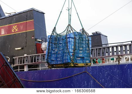 Sea of Okhotsk Russia - October 2th 2014: Sea of Okhotsk overload of frozen fish products from the sea trawler KAPITAN KAYZER in hold of a sea refrigerator ship of CRISTAL AFRICA.