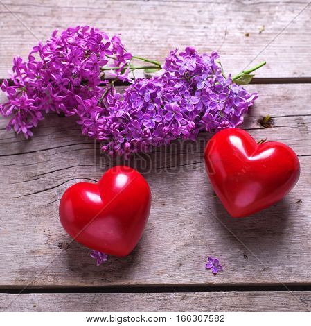 Two red hearts and fresh violet lilac flowers on aged wooden planks. Selective focus. Flat lay. Square image.